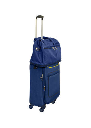 Compact blue suitcase on wheels with telescopic handle and shoulder bag. Isolated white background