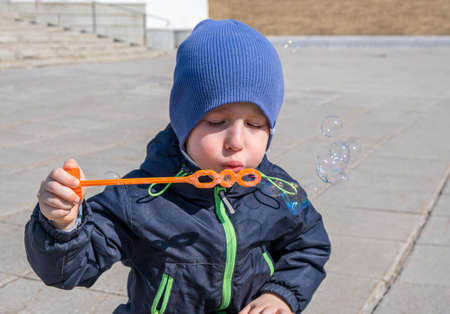 Boy in blue clothes blows soap bubbles. Spring sunny day. Small depth of field