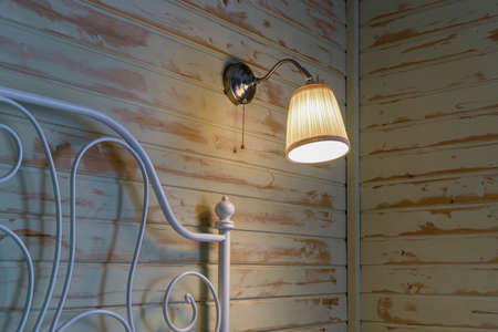 Bedroom interior evening. Fragment of headboard is made of white metal profile. Sconce with turned on bulb is on wooden wall