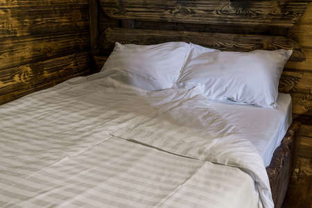Bedroom interior evening. Fragment of wooden double bed with mattress, pillows and comforter. Walls of room are covered with wooden panels Standard-Bild