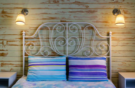 Bedroom interior evening. Fragment of double bed with pillows. Headboard is made of white metal profile. Sconce with turned on bulbs are on wooden wall