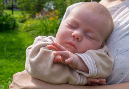Portrait of newborn baby of european type sleeping in arms of his mother Standard-Bild