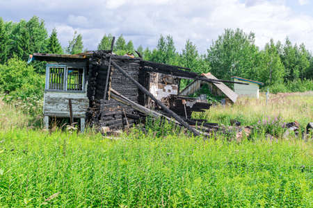 Remains of wooden country house after conflagration in abandoned suburban plot Standard-Bild