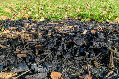 Pile of coals on ground after conflagration. Small depth of field
