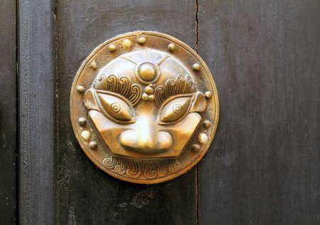 Metal sculpture on the door Mask photo