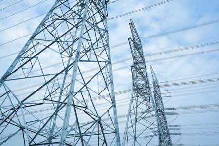 High-voltage power transmission towers in sky background photo