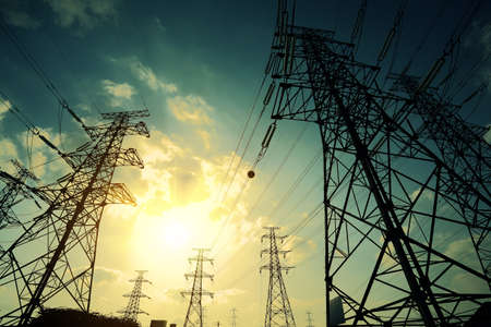 power supply: High-voltage power transmission towers in sunset sky background Stock Photo