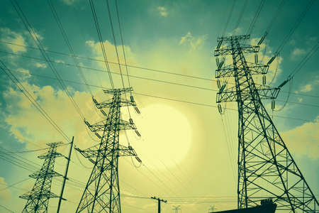 High-voltage transmission power towers in sunset sky background photo