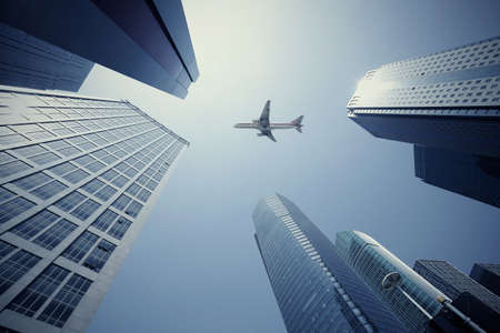 Looking up at aircraft flying over the modern urban office buildings backgrounds at Shanghai photo
