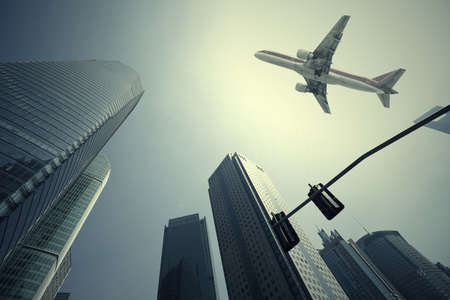 Looking up at aircraft flying over the modern urban office buildings backgrounds at Shanghai Stock Photo