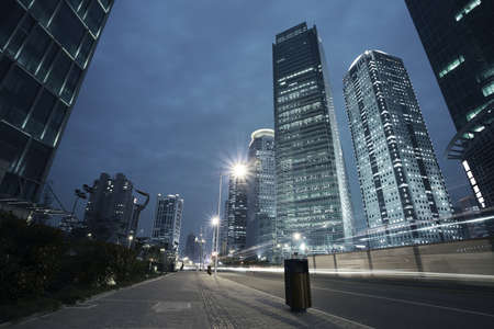 the night city: Bottom angle shooting highway car light trails of modern urban buildings   Stock Photo