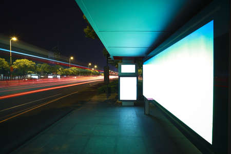 Road car light trails through at modern city advertising light boxes