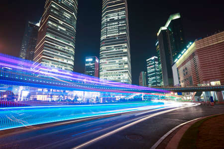 The urban background of modern office buildings car night light trails in Shanghai