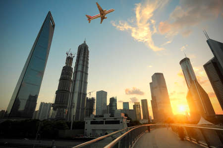 Aircraft flying over the modern city buildings over in Shanghai