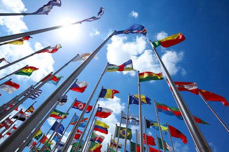 日当たりの良い青空を飛んでいる世界のすべての国の国旗