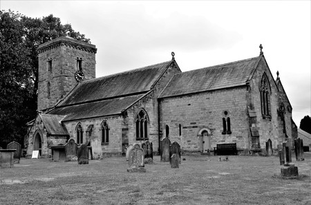 An exterior view across a graveyard to the rural church in Hovingham, North Yorkshire Foto de archivo