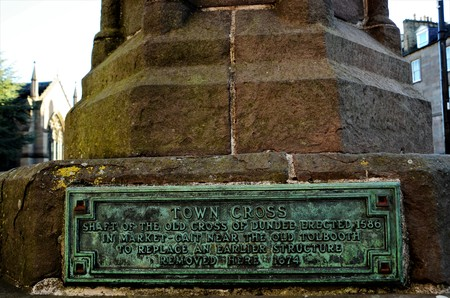A detailed view of a historical plaque on an old town cross in the city of Dundee