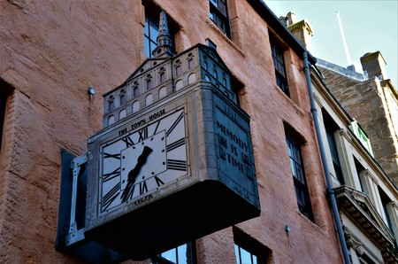 A view of a decorative clock outside an old stone building in the city of Dundee