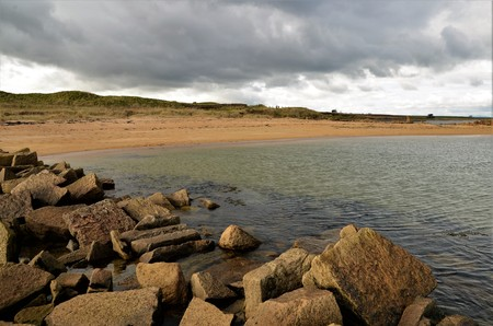 A view along the sandy and rocky seashore at Kingsbarns on the coast of Fife Stock Photo