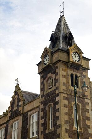 An exterior view of a clock tower building in the town of Biggar in Scotland.