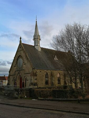 An external view of an old stone church building in the town of Carluke in Scotland.