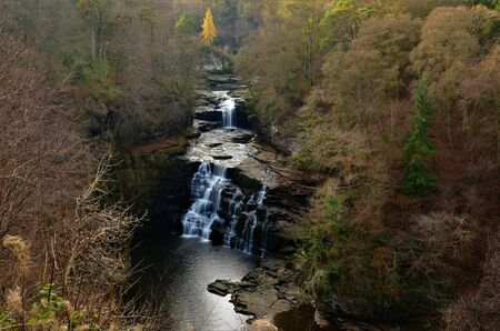A view of the falls of Clyde and the surrounding woodland near Lanark during autumn in Scotland.