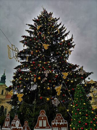 A view of a giant Christmas tree with colourful baubles in the heart of Prague during the festive period.
