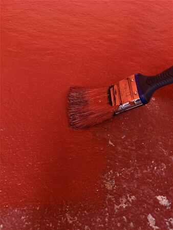 A view of a paint brush applying red doorstep paint to an exterior concrete surface.