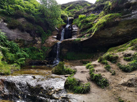 A view of the waterfall cascading over eroded rock in Glen Vale near John Knox's pulpit on the slopes of West Lomond hill in Fife, Scotland