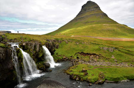 A view of the stunning Kirkjufellsfoss waterfalls in the shadow of the impressive Kirkjufell mountain on the Snaefellsness peninsula in Iceland