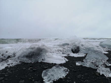 A view of iceberg fragments on a black sand beach with crashing waves at the glacial lagoon in southern Iceland 스톡 콘텐츠