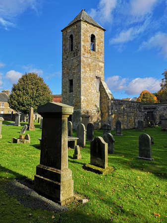An exterior view of an old stone church building and graveyard in the town of Penicuik in Scotland