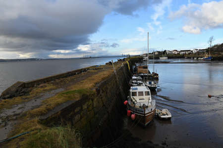A view of a variety of small boats in a harbour at Limekilns in Fife, Scotland