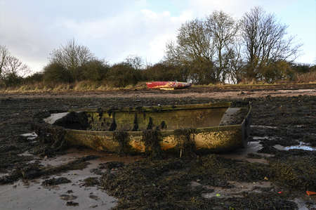 A view of old boats on a seaweed covered beach on the coast of Limekilns in Fife, Scotland. 版權商用圖片