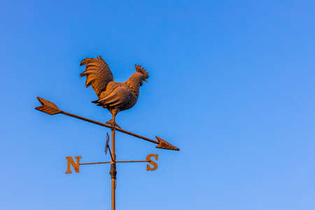 metal rusty weather cock against a blue sky pointing to south east
