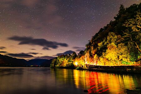 Ullswater night skies with car lights reflecting on the lake