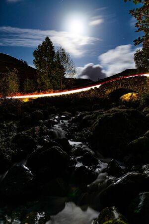 A car passing over a moonlit Ashness bridge