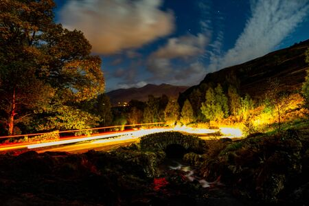 Car trails over Ashness bridge on a cloudy night
