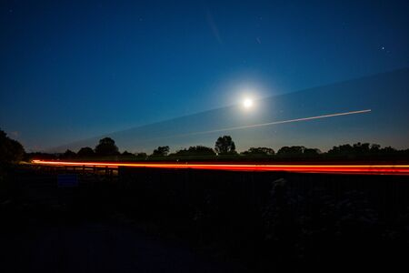 The lights of a wagon trailing past the moon on the a66 at penrith Archivio Fotografico