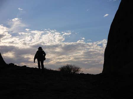 Silhouette of a male tourist hiking uphill in an Australian desert evening