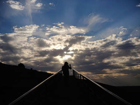 Silhouette of a male tourist hiking uphill whilst taking photos in an bright god ray evening Australian desert