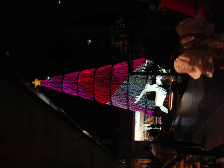 A tall colourful light up Christmas tree temporarily installed in an open square at night