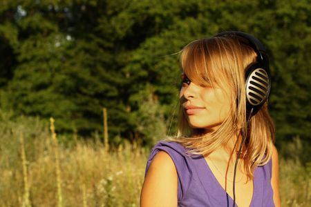 Girl walking and listening to music in the open in large headphones on wood background
