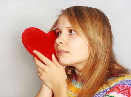 cute blonde woman pressing red fur heart to her cheek isolated on light grey background