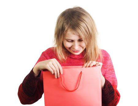 Cute blonde girl happy to find cool surprise in gift bag. Image all in red colors isolated on white background Stock Photo