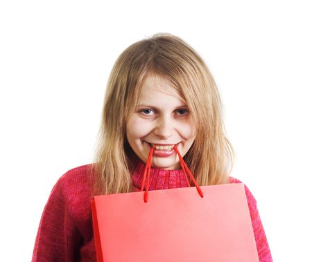 Happy cheerful blonde woman holding red shopping bag with empty space for text on it with her teeth. Image all in red colors isolated on white Stock fotó