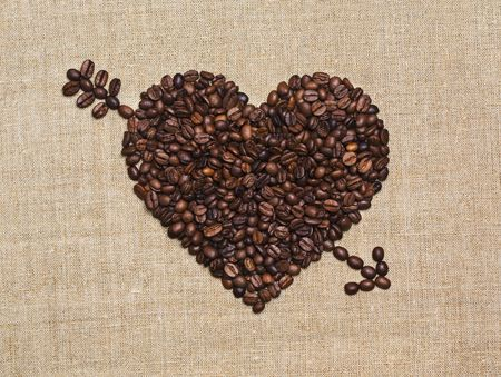 Love, coffee lover, made with love concepts. Heart with Cupid arrow made of fried coffee beans on grunge canvas.