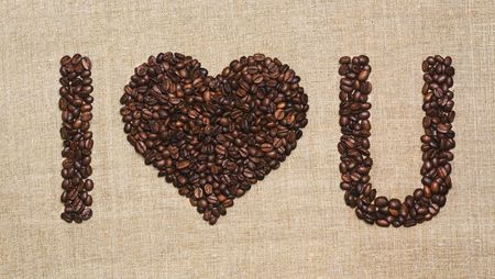 Love, coffee lover, made with love concepts. Heart with letters creating I Love You made of fried coffee beans on grunge canvas.