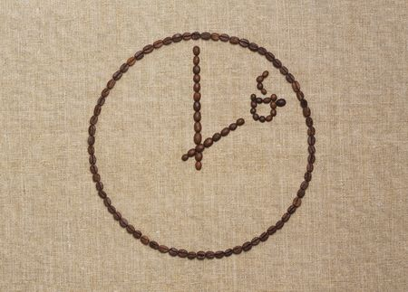 Coffee break concept. Clock with hands pointing time for coffee time made of fried coffee beans on grunge canvas