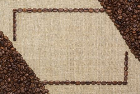 Art frame made of fried coffee beans on grunge canvas